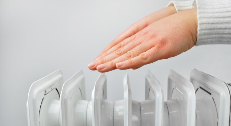 sieviete silda rokas virs radiatora